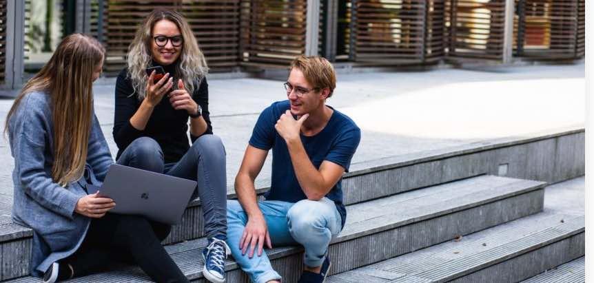 troje studentów siedzi na schodach